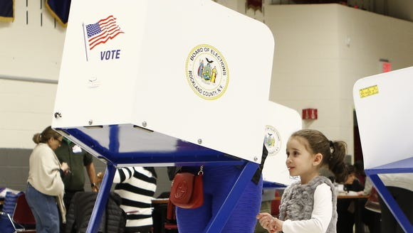 A young girl watches her mother cast her ballot at