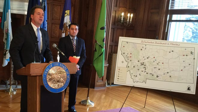 Gov. Steve Bullock unveils his budget plan Tuesday at the state Capitol as Budget Director Dan Villa looks on.