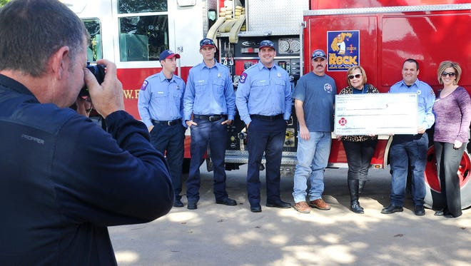 Firefighters with the Wichita Falls Fire Department pose for a picture after a check presentation to the Wichita Falls American Cancer Society and Susan G. Komen.