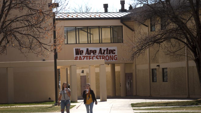 Aztec High School students pass under a banner supporting the school and community on Thursday on the school's campus.