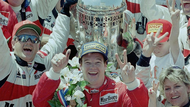 Al Unser Jr. signals his second Indianapolis 500 win from Victory Circle at the Indianapolis Motor Speedway on May 29, 1994, with the Borg-Warner Trophy behind him.