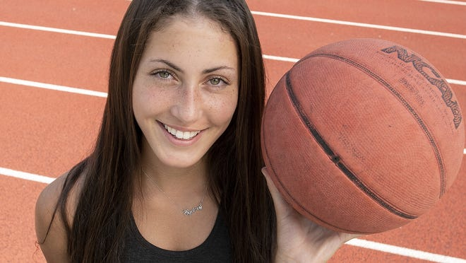 Sydney Masciarelli of Northbridge recently ran a mile while dribbling a basketball in a record 5:08.57. She is photographed on the track at Uxbridge High School on Friday.