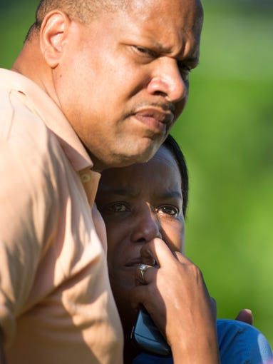 Bruce Pillow (left), who lives near the scene of a homicide at 1146 W. 35th Street, comforts Debbie Gray, a fellow neighbor, as police investigate the early morning incident, Indianapolis, Friday, June 27, 2014.