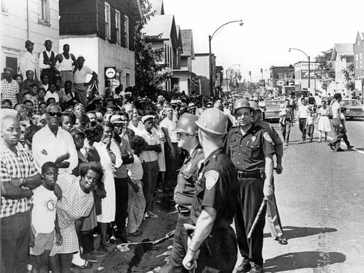 A large crowd and police face each other in the street.