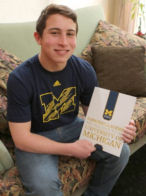 Michael Adler of Chappaqua, N.Y., wears his new T-shirt and shows off his welcome package from the University of Michigan.