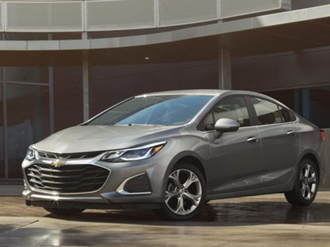 A silver 2019 Chevrolet Cruze, a compact sedan, parked outside an office building.