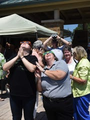 Gracie Lance (left) and Jenn Nichols react after seeing the partial solar eclipse Monday afternoon at the Donald W. Reynolds Library in Mountain Home.