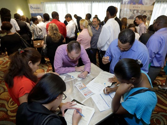 In this Oct. 22, 2014, photo, job seekers attend a
