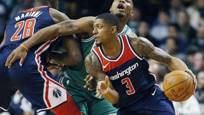 Washington Wizards' Bradley Beal (3) drives past Boston Celtics' Marcus Smart, behind, during the first quarter of an NBA basketball game in Boston, Monday, Dec. 25, 2017.