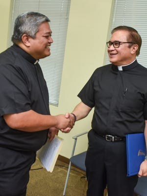 Archdiocese of Agana Delegate to the Apostolic Administrator Father Jeff San Nicolas, right, shakes hands with Monsignor James Benavente after a press conference at the Dulce Nombre de Maria Cathedral-Basilica in Hagåtña on Friday, Sept. 30. During the conference, San Nicolas announced that Benavente had been cleared of allegations of financial mismanagement and has been named pastor of St. Anthony's Church.