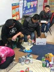 Sixth-grade students at Hurley Elementary school seperate food items that were donated as part of predicting who the Super Bowl champion was going to be.