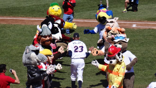 Lakewood BlueClaws player Jose Pujols runs onto the field during player introductions through a lineup of Buster's mascot friends.