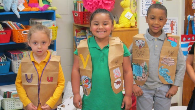 (From left) Francesca Colson, Eliana Rodriguez and Dominic Pace show off the alphabet vests they wore for the alphabet parade at Cumberland Christian School.