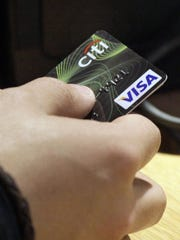 In this May 9, 2012, file photo, a Visa credit card is offered at a store in New York's Times Square. Using your credit or debit card is a very out-of-sight, out-of-mind behavior.