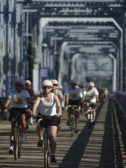 Cyclists roll across the Purple People Bridge in the