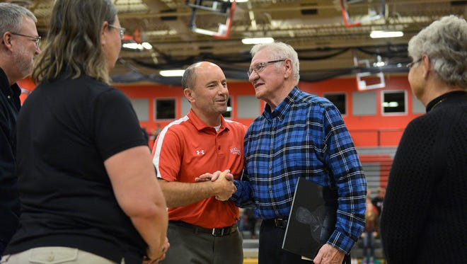 Former longtime Rocori High School head basketball coach Bob Brink, right center, is congratulated by school board members on his induction into the high school league Hall of Fame during halftime of Rocori's game Tuesday against Little Falls.