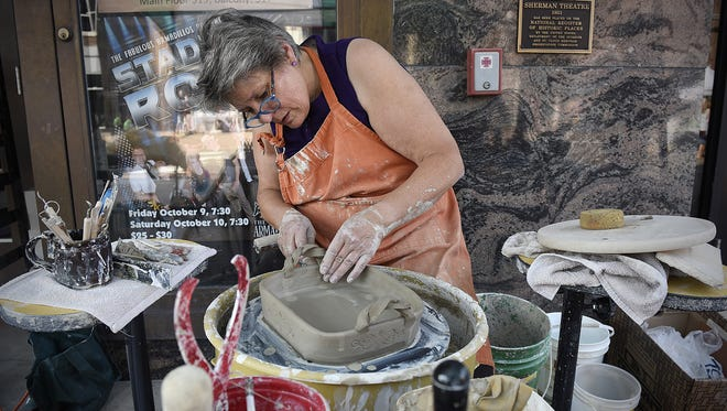 Sandy Fabian gives a pottery demonstration during last year's Sizzling Summer Art Crawl in downtown St. Cloud.