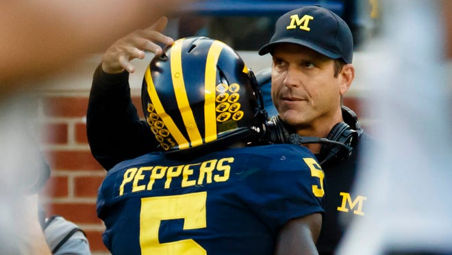 Michigan Wolverines linebacker Jabrill Peppers (5) receives congratulations from head coach Jim Harbaugh after he scores a touchdown in the second half against the Colorado Buffaloes at Michigan Stadium..