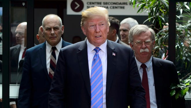 U.S. President Donald Trump leaves the G7 Leaders Summit in La Malbaie, Que., on Saturday, June 9, 2018., with White House Chief of Staff John Kelly, left, and National Security Adviser John Bolton.