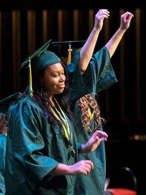Melbourne Central Catholic seniors walk across the stage to receive their diplomas during commencement exercises Friday