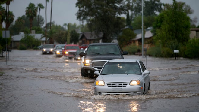 Vehicles drive through the flooded Summit Place in Chandler on Monday, Sept. 8, 2014.