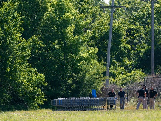Walmart employees, with the assistance of Springfield Police officers, recover shopping carts from a nearby homeless camp after most of the camps residents left following the cities plan to clear the camp.