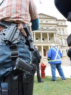 About 150 gun owners gathered on the lawn of the state Capitol on Wednesday for the annual Second Amendment March, celebrating their legal right to carry guns in the open in Michigan.