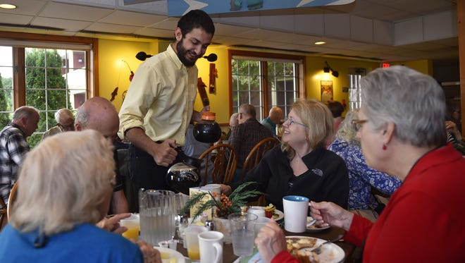 Ethemcam Korumduk of Turkey serves coffee to Sally Matthews of Wauwatosa inside the restraurant Friday, Oct. 6, 2017, at the Rowleys Bay Resort in Ellison Bay. Also at the table are Don Flick of Ft. Collins, Colo., Mary Chingwa of Waukegan, Ill., right, and Grace Grabowski of West Allis.