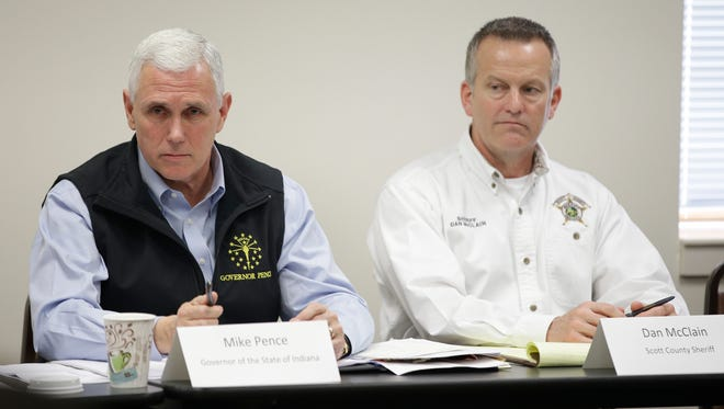 Indiana Gov. Mike Pence makes a comment as Scott County Sheriff Don McClain listens during a meeting that Pence held with local officials in Scott County to discuss an HIV outbreak in the area, Wednesday, March 25, 2015, in Scottsburg, Ind. Pence is preparing to declare a public health emergency in the southern Indiana county where 72 cases of HIV have been confirmed.