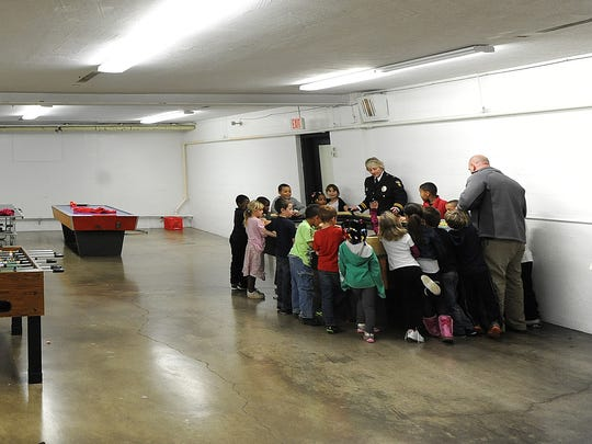 Cpt. Shari Robertson and Deputy Chief Keith Porch have the attention of the children at the Friendly House on Thursday with electric cars on a racetrack. Members of the Mansfield Police Department work with the children in a mentoring program at the facility.