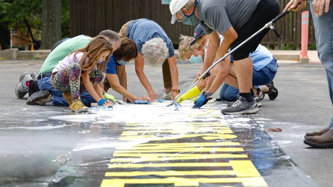 """Unitarian Universalist Church members on Monday clean white paint from a banner with the words """"Black Lives Matter"""" that has hung outside the Rockford church."""