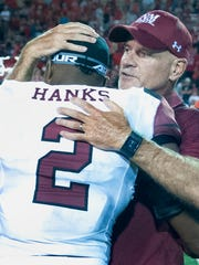 NMSU head football coach Doug Martin embraces Aggie