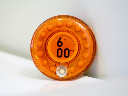 The timer on the dispenser is set to how often the person is supposed to take the medication. When the timer hits 00, the device unlocks and the person can get the pill. Turning a dial resets the timer and locks the device until the next dose can be taken.