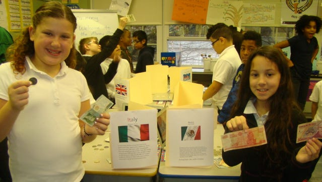 Linden School No. 2 students: Madison Pierce and Loki Crespo show off currencies viewed at recent Money Museum special program in their classroom.