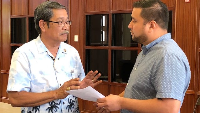 Sen. Joe San Agustin, left, on Monday confers with Sen. Fernando Esteves during a short recess of a special session to discuss San Agustin's 2 percent sales tax bill to help address a $67 million budget shortfall because of a federal tax reform law.
