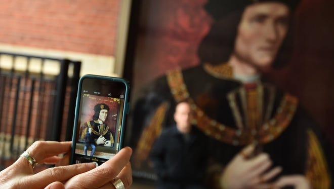A woman uses her mobile phone to take a photograph of a poster showing a portrait of England's King Richard III in Leicester Cathedral in on March 23.