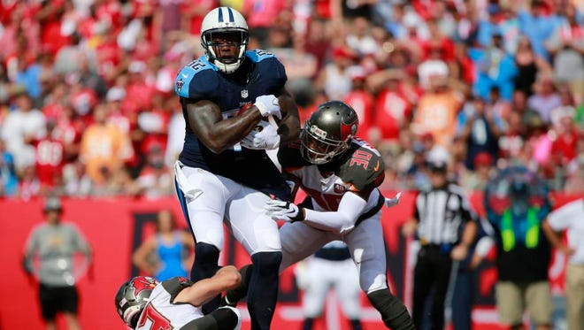 Titans tight end Delanie Walker runs in the first quarter as Buccaneers defensive back Chris Conte, left, and strong safety Bradley McDougald try to stop him.