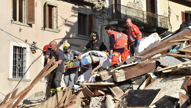 Rescuers clear debris while searching for earthquake victims in damaged buildings on Aug. 24, in Arquata del Tronto, Italy.