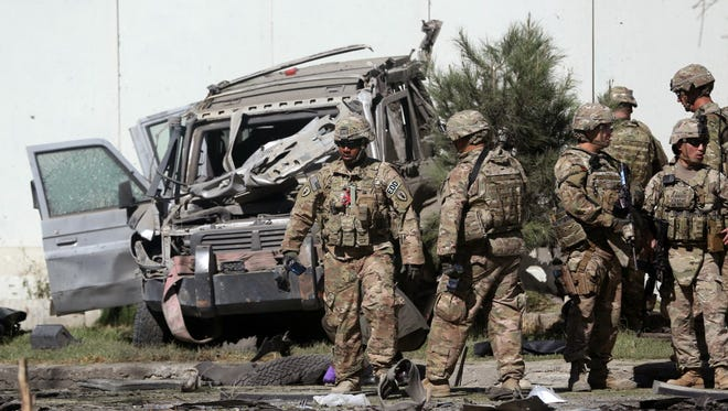 U.S. troops inspect the site of a suicide attack in Kabul, Afghanistan, in 2014.