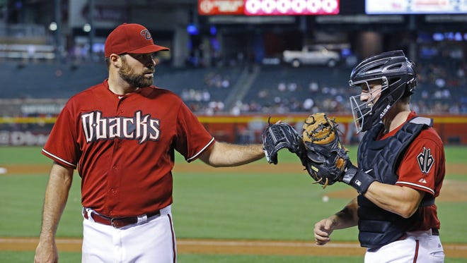 Arizona Diamondbacks starting pitcher Josh Collmenter (55) is greeted by Jordan Pacheco after eight solid innings in their 9-1 win over  the Colorado Rockies during their MLB game Wednesday, April 29, 2015 in Phoenix.