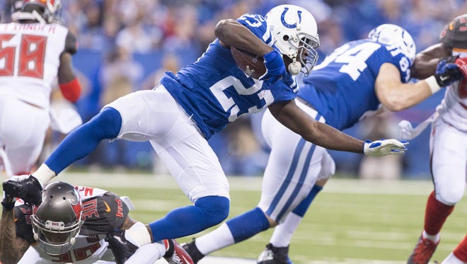 Indianapolis Colts running back Frank Gore (23) is tripped up by Tampa Bay Buccaneers free safety Bradley McDougald (30) as he rushes the ball out of the backfield during the first half of an NFL football game Sunday, Nov. 29, 2015, at Lucas Oil Stadium.