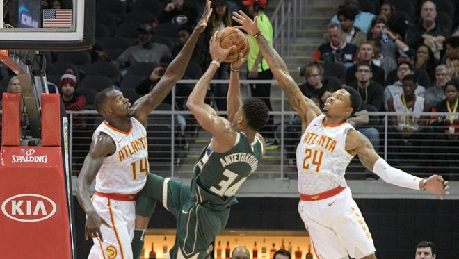 Bucks forward Giannis Antetokounmpo goes up for a shot between a pair of Hawks defenders on Sunday in Atlanta.