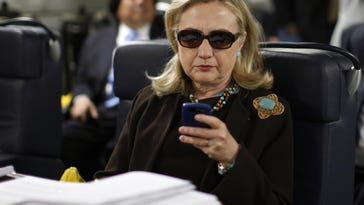 Then-Secretary of State Hillary Rodham Clinton checks her Blackberry from a desk inside a C-17 military plane upon her departure from Malta, in the Mediterranean Sea, bound for Tripoli, Libya. The private email server running in Clinton's home basement when she was secretary of state was connected to the Internet in ways that made it more vulnerable to hackers, according to data and documents reviewed by The Associated Press.