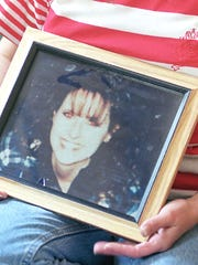 Sara Teague, with a portrait of her missing daughter Heather, is seen here in late 1996.