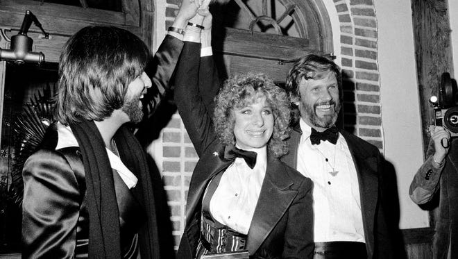 """Barbra Streisand and Kris Kristofferson, right, pose for photographers Dec. 23, 1976, at New York's Tavern-on-the-Green during a preview of the film """"A Star is Born."""" At left is Jon Peters, producer of the movie and Streisand's boyfriend."""