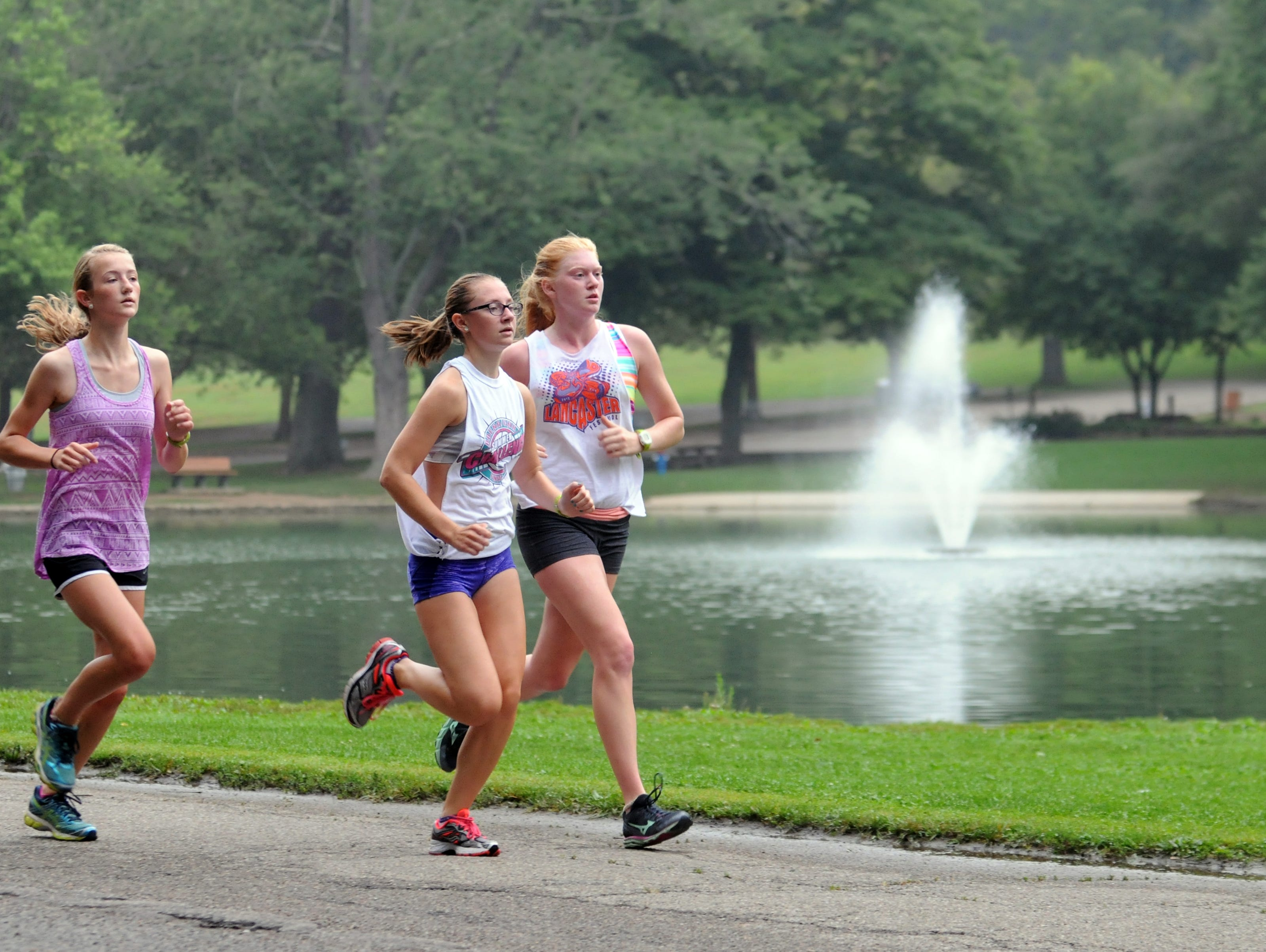 Claire McCandlish, left, Emily Johnson, center, and Heather Walker run together during practice Aug. 12 at Rising Park in Lancaster.