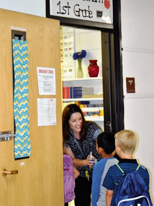 JESSICA ONSUREZ CURRENT-ARGUS   Heather Whetham, a first grade teacher at Monterrey Elementary School, greets her students one by one on Wednesday morning.   First graders across the district started school Wednesday to kick off the 2015-2016 school year.