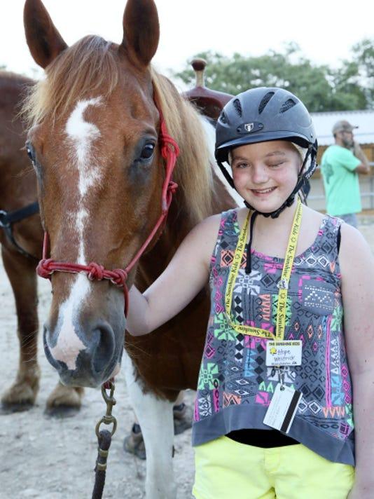 Maldonado prepares to ride a horse at the Mittman Ranch during her Sunshine Kids trip.
