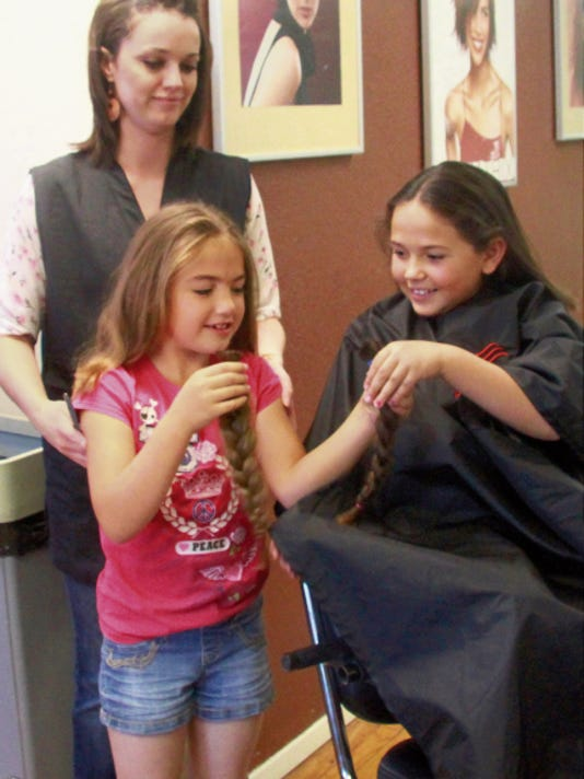SARAH MATOTT - CURRENT-ARGUS.   Sisters Amanda Melindez, 8, and Kyri Melindez, 7, take a look at their chopped off braids after their aunt Holly Gamble cut their hair for Locks of Love, an organization that specializes in making wigs out of cut hair.