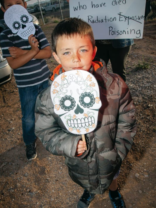 In this Daily News file photo 6-year-old Jason Najar, along with friends and family, holds a death mask near caravaners to the Trinity Site to raise awareness of possible negative health impacts stemming from the nearby atomic bomb test which took place in 1945.